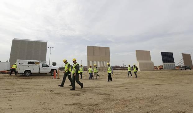 People pass wall prototypes near the border with Tijuana, Mexico, Thursday, Oct. 19, 2017, in San Diego.