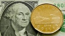 A Canadian dollar, or loonie, sits on its American counterpart (Ryan Remiorz/The Canadian Press)
