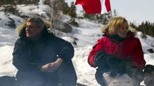Conservative Leader Stephen Harper and his wife Laureen sit to sample Arctic char and bison cooked on a campfire during a campaign stop in Yellowknife. (Frank Gunn/The Canadian Press)