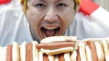Takeru Kobayashi poses for pictures after winning Nathan's Famous Hot Dog Eating Competition Tuesday, July 4, 2006, in Coney Island, New York. Kobayashi won his sixth straight title by beating his own record and eating 53 and 3/4 hot dogs. (SETH WENIG/(AP Photo/Seth Wenig))