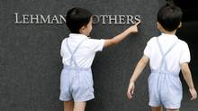 Children play with a sign of Lehman Brothers Holdings at the company's branch in Tokyo September 16, 2008. (Toru Hanai)