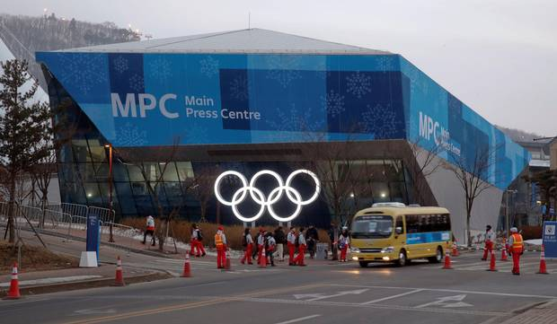 A shuttle bus drives past volunteers in front of the Main Press Center at the Alpensia mountain resort in Pyeongchang on Feb. 18, 2018.