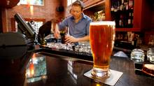 A glass of beer sits on the bar as manager Ryan McGregor pours another drink at Canoe Brewpub in Victoria. (Deddeda Stemler)