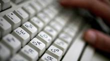 A person types on a computer keyboard with both Latin and Cyrillic letters. (Stoyan Nenov/Reuters)