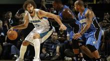 New Orleans Hornets centre Robin Lopez (L) controls the ball over Orlando Magic centers Glen Davis (2nd R) and guard Jameer Nelson (R) during their exhibition NBA game in Mexico City October 7, 2012. (HENRY ROMERO/REUTERS)