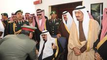 Saudi Arabia's King Abdullah (seated) is greeted by a Saudi officer on his arrival at Riyadh airport in this February 23, 2011 file photo. (HO/REUTERS)