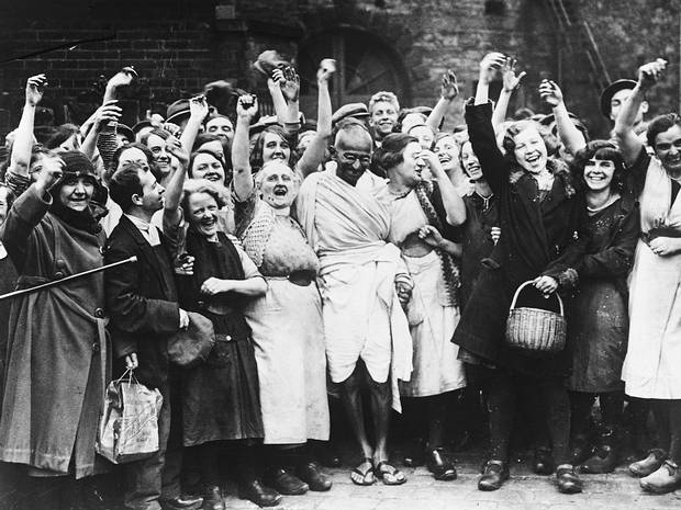 Gandhi acknowledges the cheers of young women workers outside Greenfield Mill in Darwen, Lancashire as part of his study of labour conditions in the English cotton industry. UK, 1931.