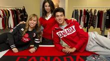 Hudson Bay Company fashion director Suzanne Timmins (centre) poses with trampoline athlete Karen Cockburn (left) and swimmer Tobias Oriwol along with The Bay's Olympic inspired clothing in Toronto on Wednesday November 2, 2011. (Frank Gunn)