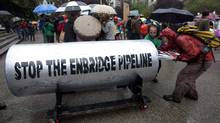 Protesters load a giant piece of pipeline with their placards following a protest outside the Vancouver Art Gallery in downtown Vancouver on Aug. 31, 2010. The pipeline was brought there by opponents of the Northern Gateway Pipeline Project, which would see a gas pipeline built in northern B.C. It's being called a nation-builder, nation-divider and non-starter, depending on who's talking. (Jonathan Hayward/The Canadian Press/Jonathan Hayward/The Canadian Press)