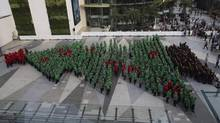 Wearing red, green and black hoodies, 852 students in Bangkok break the Guinness World Record for forming the largest human Christmas tree. (Sakchai Lalit/AP)