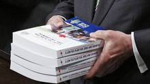 Finance Minister Jim Flaherty holds copies of his budget in the House of Commons on March 22, 2011. (CHRIS WATTIE/REUTERS)