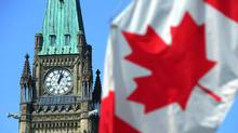 The Peace Tower and a Canadian flag are seen on Parliament Hill in Ottawa. (Sean Kilpatrick/THE CANADIAN PRESS)