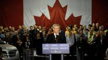 Prime Minister Stephen Harper speaks in front of Ford of Canada production workers at the Oakville, Ontario assembly plant, where he announced a five-year, $250-million auto industry subsidy renewal, on Jan. 4. (STRINGER/REUTERS)