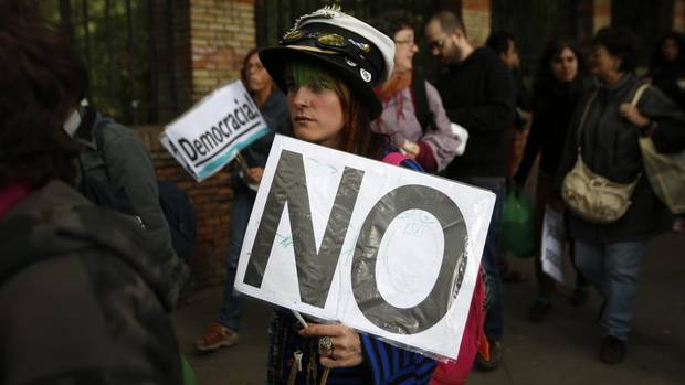 A protestor carries a sign as demonstrators walk towards Spain's parliament in Madrid Sept. 25, 2012 to protest the government's tough 2013 budget that will cut into social services as the country teeters on the brink of a bailout. (ANDREA COMAS/REUTERS)