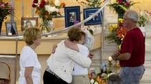 Two women embrace inside Ste-Agnès Church in Lac-Mégantic, Que. on July 13, 2013. (Peter Power/The Globe and Mail)