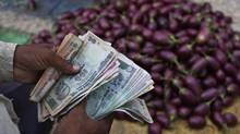 India's rupee has lost about a fifth of its value against the U.S. dollar since May. It plunged nearly 4 per cent last Wednesday alone. The clouded fiscal and economic prospects of such deeply troubled countries as India, Brazil, Turkey, Indonesia and South Africa have nervous investors keeping their fingers on the sell buttons. (Rajesh Kumar Singh/AP)