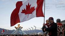 A Canadian mother and her child proudly wave the Maple Leaf in front of the Olympic cauldron after Canada's gold-medal hockey victory over the United States in Vancouver on Feb. 28, 2010. (CHRIS HELGREN)
