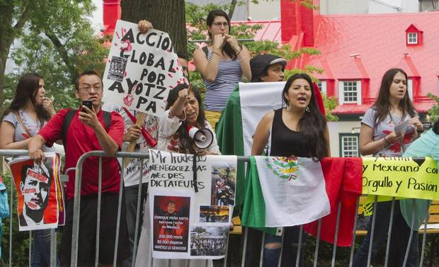 People protest against a visit by Mexico President Enrique Pena Nieto in Quebec City, Monday, June 27, 2016.