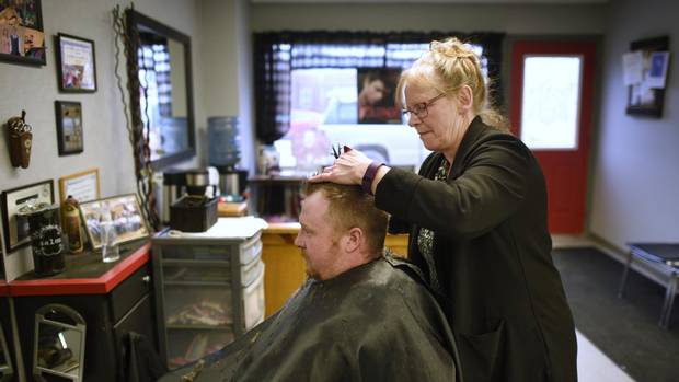 Cathy Slear, co-owner of the Creative Hair Boutique in Shelburne, trims Jeff Coyle's hair. Slear believes a bowling alley would be a good addition to the town since there's not much for people to do locally. Coyle lives in nearby Honeywood but has also noticed the recent growth in the population of Shelburne.