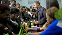 U.S. President Barack Obama pitches in a Washington foodbank on Nov. 23, 2011. (JIM WATSON/AFP/Getty Images)