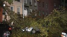 A fallen tree branch sits on a car blocking East 74th St. between Lexington Avenue and Third Avenue on Manhattan's Upper West Side on Monday, Oct. 29, 2012. (Willie Regan/AP)