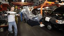 A Chrysler auto worker uses an ergo-arm to load the seats into Chrysler minivans. The auto sector was among those reporting declines in wholesale sales in April. (REBECCA COOK/Reuters)