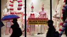 Pedestrians pass a shop window display advertising Thanksgiving sales in New York November 25, 2009. (FINBARR O'REILLY/REUTERS)
