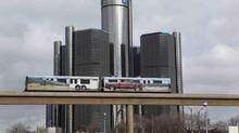 Two cars of the 'people mover' public rail are seen covered with a advertisement for the 2014 Chevy Silverado pickup truck as they move past General Motors World Headquarters in Detroit, Jan. 11, 2013. (REBECCA COOK/REUTERS)