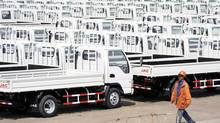 A worker walks past Chinese trucks for exporting at a port of Liangyungang, Jiangsu province, March 31, 2013. China's official manufacturing purchasing managers' index (PMI) released by the National Bureau of Statistics rose to an 11-month high of 50.9 in March, above the 50-point level that indicates growth on the month. (CHINA DAILY/REUTERS)