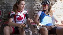 Canadian Olympian Clara Hughes (left) puts on her shoes as she chats with teammate Joëlle Numainville before going out on a training ride in Horsley, Sussex, England on Wednesday July 25, 2012. (THE CANADIAN PRESS)