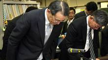 Japan's megabank Mizuho Financial Group president Takashi Tsukamoto (L) bows his head at a press confgerence at the bank of Japan in Tokyo on May 23, 2011 . Mizuho unveiled a restructuring plan in an effort to restore client confidence following a computer breakdown that caused a massive stall in money transfers. AFP PHOTO / JIJI PRESS (STR)