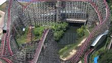 This aerial photo shows the Texas Giant roller coaster at Six Flags Over Texas where a woman fell to her death, Saturday, July 20, 2013, in Arlington, Texas. Investigators will try to determine if a woman who died while riding the roller coaster at the amusement park Friday night fell from the ride after some witnesses said she wasn't properly secured. (Louis DeLuca/AP)