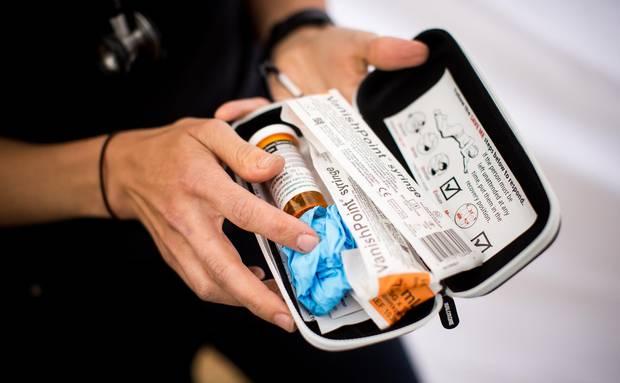 Hirsh holds a Naloxone injection kit during a overdose awareness program.