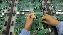 A Celestica employee works on a motherboard at the company's facility in Dongguan, China, in this 2009 file photo. (Vincent Yu/AP)