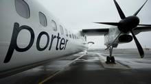 A Porter Airlines Inc. Q400 plane stands on the tarmac at Billy Bishop Toronto City Airport in Toronto, Ontario, Canada, on Wednesday, April 10, 2013. Porter Airlines Inc., the Canadian carrier that now flies only turboprops, plans to add its first jets, at least 12 Bombardier Inc. CSeries airliners, to start long-haul flights in an expanded challenge to Air Canada and WestJet Airlines Ltd. (Norm Betts/Bloomberg)