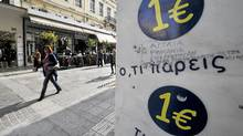 A woman walks past a '1 Euro' shop in Athens in November, 2011. Pro-austerity parties in Greece failed to win enough support from voters to form a government this month, and neither did their anti-austerity opponents. (Louisa Gouliamaki/AFP/Getty Images/Louisa Gouliamaki/AFP/Getty Images)