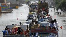 Trucks and cars cross through a flooded highway in Muzaffargrah, in central Pakistan on Sunday, Aug. 22, 2010. (Khalid Tanveer/Khalid Tanveer/The Associated Press)