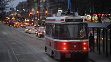 A northbound Spadina streetcar picks up passengers near Front St West in downtown Toronto on February 27 2012. (Fred Lum/The Globe and Mail)