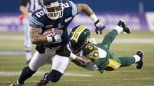 Toronto Argonauts wide receiver Chad Owens, left, tries to break a tackle from Edmonton Eskimos centre back Rod Williams, right during first half CFL Eastern Conference semi final action in Toronto on Sunday, Nov. 11, 2012. (Nathan Denette/THE CANADIAN PRESS)