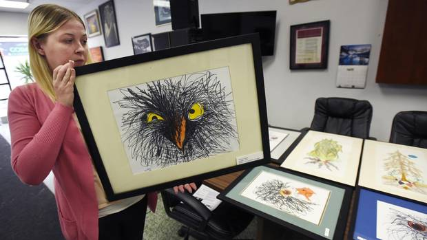Natasha Smith, employment co-ordinator for The Bridge, holds Angry Birds, a work by Wayne Forest, at show of prisoner art in Brampton, Ont.