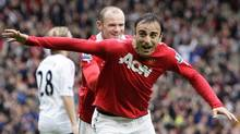 Manchester United's Dimitar Berbatov, right, celebrates with teammate Wayne Rooney after scoring his second goal against Liverpool during their English Premier League soccer match at Old Trafford Stadium, Manchester, England, Sunday Sept. 19, 2010. (Jon Super/AP)