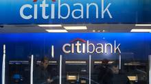 Customers wait at an ATM at a Citibank branch in New York. (KEITH BEDFORD/REUTERS)