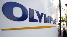 A man walks past a sign of Olympus Corp outside the company's showroom in Tokyo November 4, 2011. (YURIKO NAKAO/YURIKO NAKAO/REUTERS)