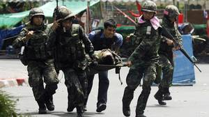 Thai soldiers carry a wounded comrade on a stretcher.