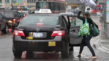 A women walks through a puddle on Bathurst Street in Toronto to catch a taxi. (Deborah Baic/The Globe and Mail)
