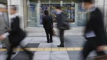 A man looks at a stock quotation board outside a brokerage in Tokyo in this Nov. 7, 2012, file photo. (Toru Hanai/REUTERS)