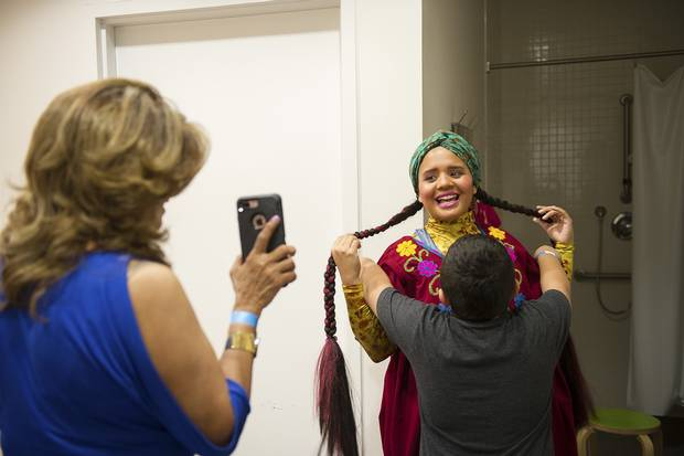 Pimienta, gets a hug from nephew Orlando Pimienta, 6, as her mother, Rosario Paz, shows her a photo.