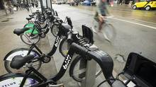Cyclists ride past a Bixi bicycle stand in Toronto on Tuesday, April 16, 2013. (Kevin Van Paassen/The Globe and Mail)