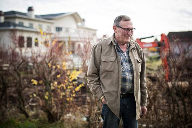 The mansion next door looms behind beekeeper Bob Fisher on his property in Richmond, B.C.