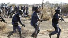 Policemen react after firing shots at protesting miners outside a South African mine in Rustenburg, 100 kilometres northwest of Johannesburg on August 16, 2012. (SIPHIWE SIBEKO/REUTERS)